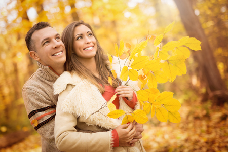 embraced: Portrait of a beautiful young couple in sunny forest in autumn colors. They are at embraced and holding yellow leaf.