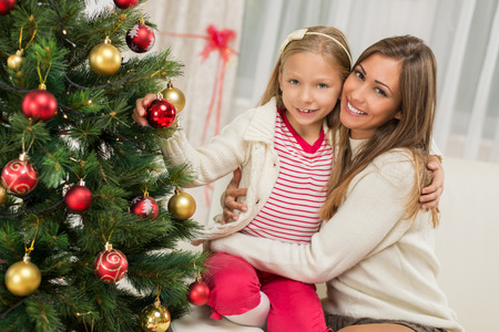 decorating christmas tree: Young mother and her daughter decorating Christmas tree at home. Stock Photo