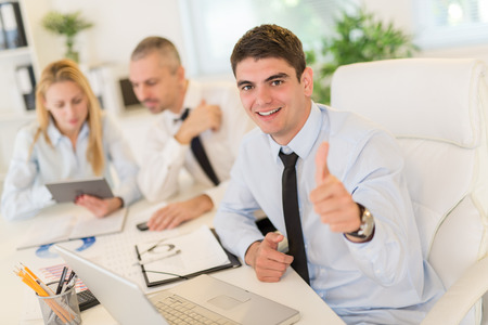 business manager: Business people having a meeting. Focus is on happiness young businessman with thumb up and looking at camera. Selective focus. Stock Photo