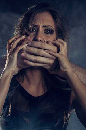 panicked: Young woman abuse victim with mans abuser hands on her mouth looking at camera Editorial