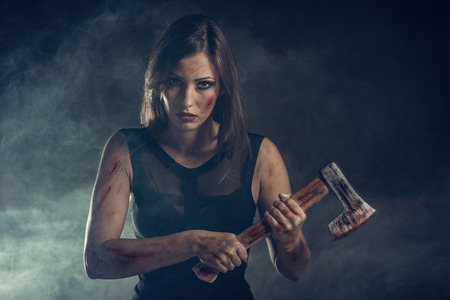 woman warrior: Beautiful dangerous girl with rusty axe. Looking at camera. Stock Photo