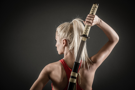 fighter: Pretty girl with a serious expression on her face drawing katana.