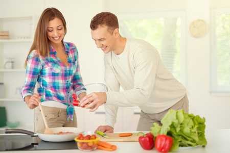 domestic kitchen: Beautiful young couple cooking healthy meal in the domestic kitchen.