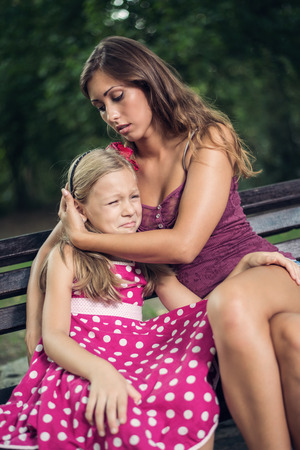 consoling: Young beautiful mother consoling her cute daughter at bench in the park. Stock Photo