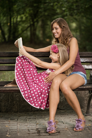 mother on bench: Happy cute little girl and her mother reading book at bench in the park.