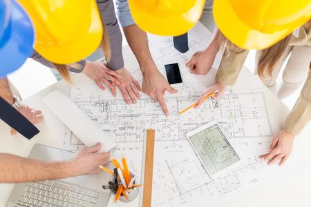 Vista superior de las cuatro arquitecto de éxito la comprobación de los planos arquitectónicos.