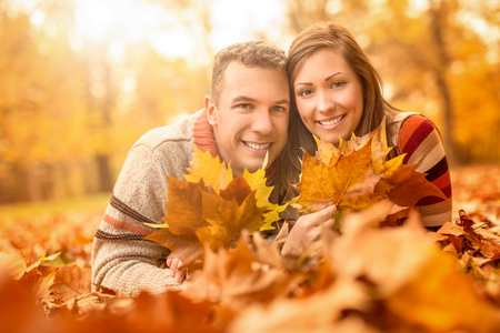 embraced: Beautiful young couple in sunny forest in autumn colors. They are lying on the fall meadow at embraced and holding yellow leaves. Looking at camera. Stock Photo