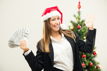 Happiness young businesswoman wearing santa hat and holding money. Stock Photo