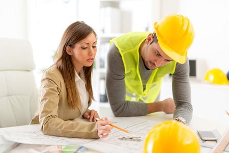 arquitecto: jóvenes arquitectos con éxito discutir los planes de construcción en el cargo. Foto de archivo