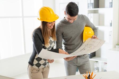 planificacion: Arquitecto sonriente mirando los planos de arquitectura en la oficina. Foto de archivo