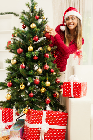decorating christmas tree: Happy beautiful young woman decorating christmas tree at home. Stock Photo