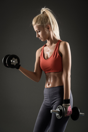 tricep: Young beautiful fit woman doing exercise for biceps. Stock Photo