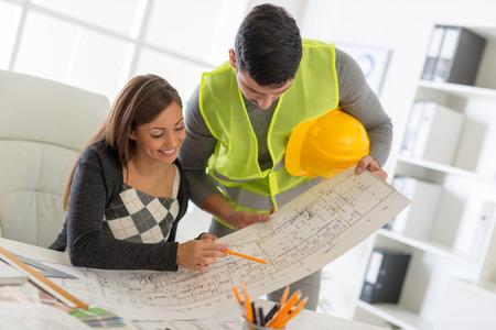 arquitecto: j�venes arquitectos con �xito discutir los planes de construcci�n en el cargo. Foto de archivo