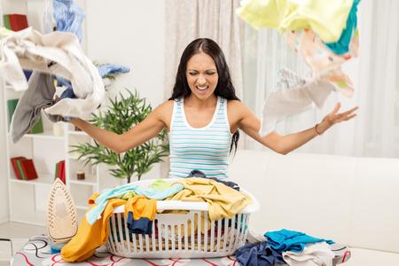 casalinga: Giovane casalinga frustrata in piedi davanti l'asse da stiro e disperde la biancheria dal cesto della biancheria.