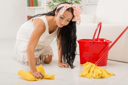 scrubbing: Young beautiful maid scrubbing floor.