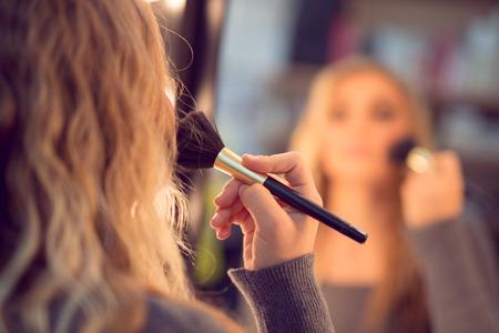 blush: Cute girl in front of mirror applying blush.