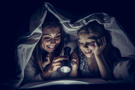 Smiling mother and her daughter reading book under bed cover and holding a flashlight. Archivio Fotografico