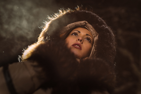 fur hood: Beautiful young woman in winter jacket with fur hood looking away and thinking.