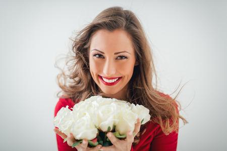 rosas blancas: Retrato de una joven y bella mujer sonriente celebración manojo de rosas blancas y mirando a la cámara. Foto de archivo