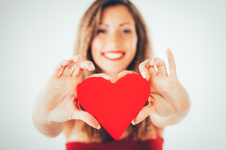 Close-up of a beautiful smiling girl holding a red heart. Selective focus. Focus on the heart.