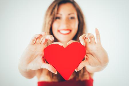 the human heart: Primer plano de una hermosa ni�a sonriente sosteniendo un coraz�n rojo. enfoque selectivo. Centrarse en el coraz�n.