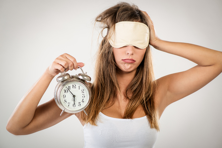 sleeping mask: Beautiful young woman with sleeping mask holding alarm clock. She is tired and lazy in morning.