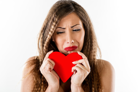 heart white: Beautiful unhappy girl crying and holding broken red heart. Valentines Day concept.
