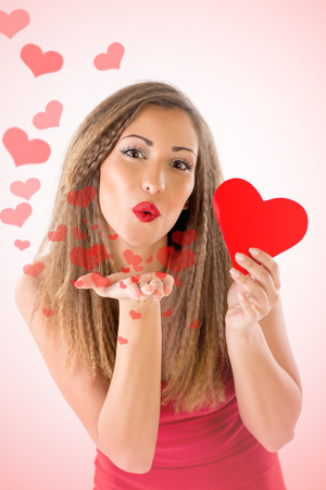 human lips: Beautiful smiling girl holding red heart. She is sending a kiss with many flying heart. Looking at camera.