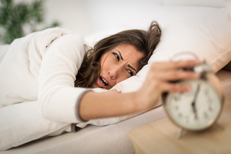 frowning: Beautiful young woman frowning in bed and holding hand on alarm clock. She is doesnt want to wake up. Stock Photo