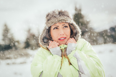 frozen winter: Beautiful young frozen woman skier in winter vacations, standing and looking away. Stock Photo