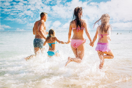 fun: Happy family having fun on the beach. They with holding hands running and splashing in the sea.
