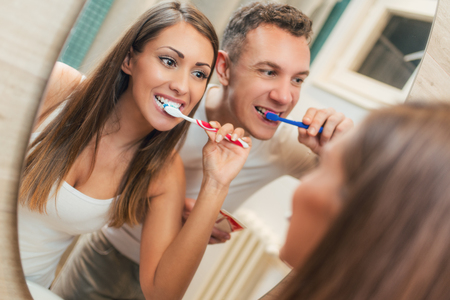 Portrait of a beautiful young happy couple brushing teeth in front of their bathroom mirror. Selective focus. 免版税图像