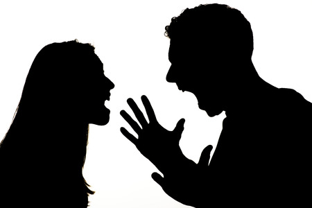 victim: Silhouette of couple violence. They are angry and shouting face to face.