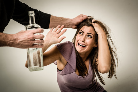abusing: Angry aggressive drunk husband is physically abusing his wife.