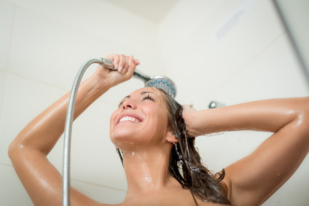 woman washing face: Happiness shower woman washing face and hair in while showering under shower head.