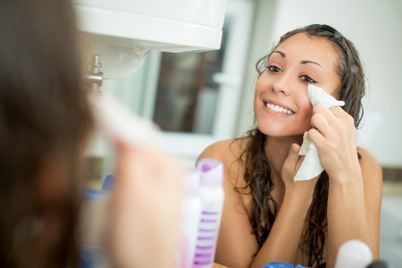 Beautiful smiling young woman removing make up with a facial wipe in front of mirror. Standard-Bild