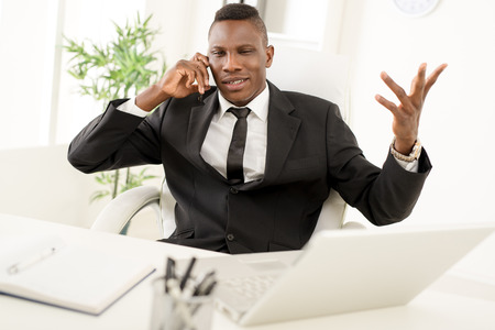 displeased businessman: Angry African businessman in the office using mobile phone.