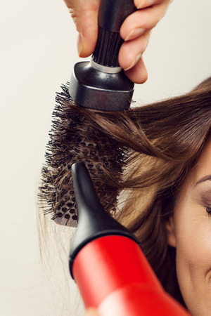 long brown hair: Hairdresser drying long brown hair with round brush.