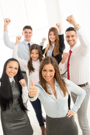 Grupo de hombres de negocios exitosos de pie con el pulgar hacia arriba y la cámara lookingat. Foto de archivo