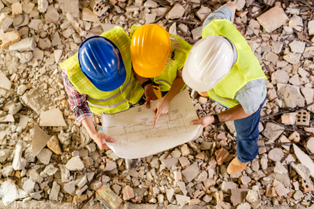 damaged: Three construction architects review plan in building damaged in the disaster. Stock Photo