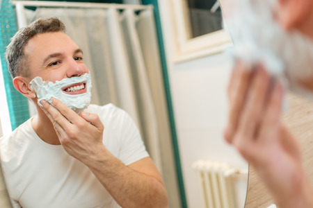 shaving cream: Portrait of a beautiful young man applying shaving cream in front of his bathroom mirror. Selective focus.