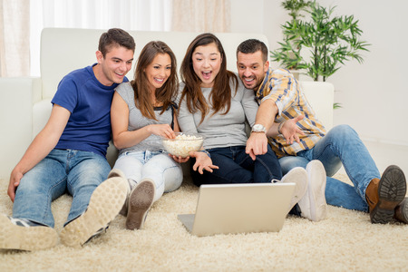 they are watching: Four cheerful best friends having nice time in an apartment. They are watching movie together. Stock Photo