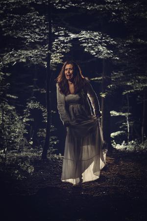 30a3e0cac  61105986 - Joven mujer asustada caminando por el bosque por la noche en  vestido blanco y gritando. Escena de horror.