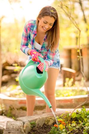 Lächelnde junge Frau, die Bewässerung der Blumen im Garten.