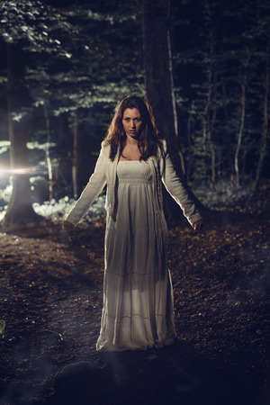 Young lonely woman walking through the forest at night in white dress. Looking at camera.