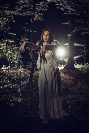 bdd748229  61243790 - Joven caminando por el bosque de noche en el vestido blanco con  los brazos extendidos en frente del cuerpo.