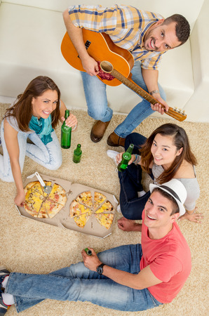 enjoing: Four cheerful friends enjoing with guitar in an apartment. They drinking beer and eating pizza. Looking at camera.