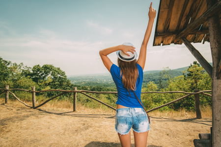 raised viewpoint: Cheerful woman on summer travel vacation standing by viewpoint with outstretched arm. Rear view.