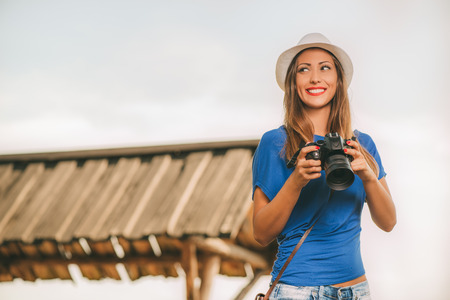 viewpoint: Young beautiful woman standing by viewpoint and holding digital camera. Stock Photo