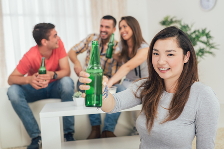Close up of a young Japanese girl smiling at home party with beer and cheers. Her friends in the background. Selectiv focus. Focus on foreground.